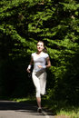 Beautiful running girl. Female runner jogging during outdoor workout on trail in park or forest. Royalty Free Stock Photo