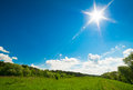 Beautiful rural landscape green meadow blue sky with clouds sun shines with rays and flare Stock Images