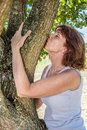 Beautiful 50s woman kissing tree in harmony with nature