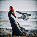 Beautiful sad goth girl with cloth in hands standing on sea shore Royalty Free Stock Photo