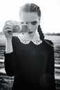 Beautiful sad young girl photographing on vintage film camera. Black and white Royalty Free Stock Photo