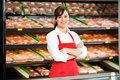 Beautiful saleswoman standing arms crossed in portrait of at counter butcher s shop Stock Photography