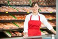 Beautiful saleswoman standing at counter in portrait of smiling while butcher s shop Stock Photos