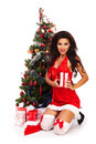 Beautiful santa helper next to christmas tree woman Stock Photo