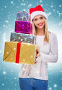 Beautiful santa woman holding gift box and credit card,snowfall background Royalty Free Stock Photo