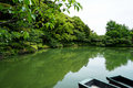 Beautiful scene of lush green japanese garden mountain landscape with shades of green plant, boats, lotus pond, etc. Royalty Free Stock Photo