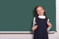 Beautiful school girl with pigtail smiled near blank chalkboard background, dressed in classic black suit, education concept Royalty Free Stock Photo