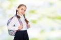Beautiful schoolgirl with a backpack behind her shoulders.