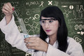 Beautiful scientist analysing liquid at workplace is the inside flask on written chalkboard background Stock Photos