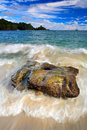 Beautiful sea coast landscape with waves and stone green island in the background big stone in the water ocean with dark blue s Stock Photos