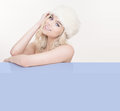 Beautiful seductive woman in cool winter white blond wearing a fashionable fur hat and leaning on a blank blue placard with an Royalty Free Stock Photo