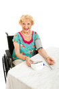 Beautiful senior takes own blood pressure woman in wheelchair taking her with a home machine white background Royalty Free Stock Photography