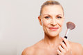 Beautiful senior woman applying makeup holding brush Stock Photos