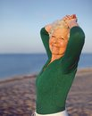 Beautiful senior woman standing relaxed at the beach portrait of with ocean and sky as blurred background and copy space Royalty Free Stock Photography