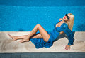 Beautiful sensual blonde with fashionable sunglasses relaxing at the pool. Attractive long hair woman in bright blue long dress Royalty Free Stock Photo