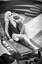 Beautiful sensual blonde with fashionable sunglasses relaxing at swimming pool with a juice. Attractive long fair hair woman Royalty Free Stock Photo