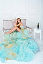 Beautiful sensual blonde woman in gorgeous long dress holding glass of white wine with bottle standing on the table