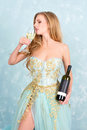 Beautiful sensual blonde woman in gorgeous long dress holding glass of white wine and bottle. Young girl celebrating