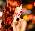 Beautiful sensual woman with long red hairs and nails over art blink night lights Royalty Free Stock Photo