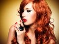 Beautiful sensual woman with long red hairs and nails at studio Stock Image