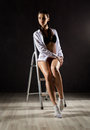 Beautiful sensual young woman with pigtail in men`s shirt sitting on a stepladder on a gray background