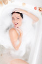 Beautiful sexual attractive young woman sensual girl lying relaxing and enjoying in the spa bath with foam happy smiling Royalty Free Stock Photo