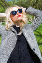 Beautiful sexy blond girl with red lips in sunglasses walking in the garden of a bright sunny day Royalty Free Stock Photo