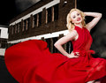 Beautiful sexy blond girl wearing a long dress portrait of elegant red when dancing in urban back alley with stylish hair and Royalty Free Stock Photography