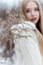 Beautiful sexy blonde girl with long hair, full lips in a white coat walking in the winter woods Royalty Free Stock Photo