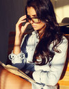 Beautiful sexy business woman with dark curly hair reading a book fashion photo of wearing jeans shirt watch glasses sitting at Royalty Free Stock Images