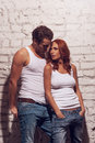Beautiful sexy couple looking at each other wearing white t shirts and jeans Stock Photos