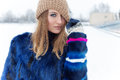 Beautiful sexy cute cheerful happy girl pulled a hat winks with bright makeup on eyes with bright blue coat bright winter day Royalty Free Stock Photo