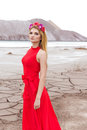 Beautiful sexy cute girl with long blond hair in a long red evening dress with a wreath of roses and orchids in her hair standing Royalty Free Stock Photo