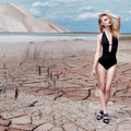 Beautiful sexy cute girl in swimsuit fashion shoot in desert with dry cracked ground background mountains under Royalty Free Stock Photo