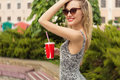 Beautiful cute happy smiling girl with a glass in his hand in sunglasses drinking a Coke on a sunny hot day Royalty Free Stock Photo
