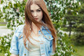 Beautiful sexy cute sweet girl with long red hair and green eyes in a denim jacket near a flowering tree in the park the wind Royalty Free Stock Photo