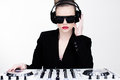 Beautiful sexy disc jockey at her deck standing over the turntables wearing modern sunglasses and headphones with pouting red lips Royalty Free Stock Images