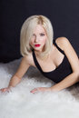 Beautiful sexy elegant striking blonde woman with bright makeup red lips in a black dress lies on the white fur the studio Stock Image