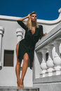 Beautiful fashion model woman posing in black dress outdoor Royalty Free Stock Photo