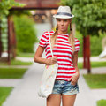 Beautiful sexy female in jeans shorts and striped t-shirt, in hat, outdoors. Tanned girl in summer Royalty Free Stock Photo