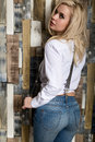 Beautiful sexy girl with big boobs in a vintage blue jeans and white shirt poses near a wooden wall. Royalty Free Stock Photo
