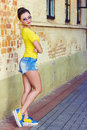 Beautiful sexy girl with black hair in sunglasses shorts and yellow t shirts standing by a brick wall Royalty Free Stock Photography