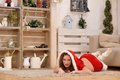 Beautiful girl with curly hair in Santa Claus clothes posing on warm rug Royalty Free Stock Photo