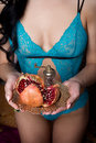 Beautiful sexy girl with dark long hair in lingerie holding lace underwear pomegranate fruit on a plate in the hands of Royalty Free Stock Photo
