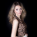 Beautiful sexy girl in leopard dress in bright makeup in the Studio on a black background Royalty Free Stock Photo