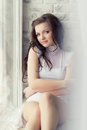 Beautiful sexy girl with long dark hair in a white body sits at home by the window Royalty Free Stock Photo