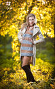 Beautiful sexy girl with long leather boots and short dress posing in park in autumn day beautiful elegant woman in autumn park Royalty Free Stock Photography