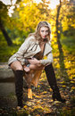 Beautiful sexy girl with long leather boots and short dress posing in park in autumn day beautiful elegant woman in autumn park Stock Images