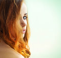 Beautiful sexy girl with long red hair with green eyes looking out over the shoulder on a white background Royalty Free Stock Photo