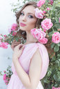 Beautiful sexy girl in a pink dress standing in the garden roses in a sunny bright summer day with a gentle make-up and bright puf Royalty Free Stock Photo
